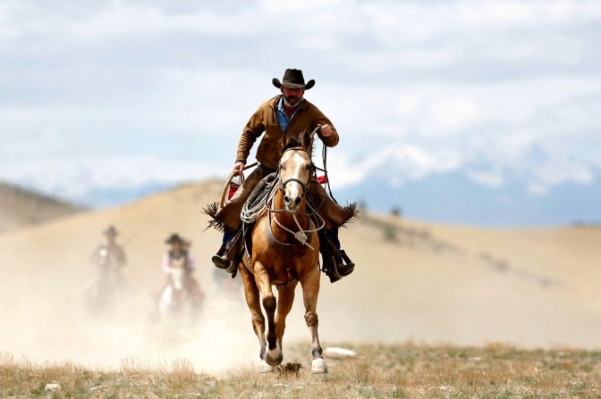 A cowboy and his horse kick up dust out on the range. Photo Credit: PictureNix.com.