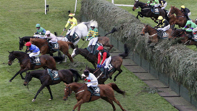 Synchronized riden by Tony McCoy, centre, wearing green silks with yellow bands, falls after jumping Becher's Brook. (Photo: AP/Scott Heppell)