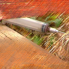 Used syringe disposed of behind a barn.