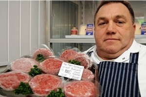 Butcher Clinton Roberts who has been involved in the industry as an independent butcher for more than 40 years holds a platter of beef burgers with a note saying 100% beef.  Hold your horses ... not quite. Google image.