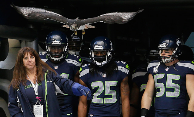Taima the Hawk leads Seattle Seahawks including cornerback Richard Sherman on to the field before an NFL football game against the St. Louis Rams, Sunday, Dec. 30, 2012, in Seattle. Photo by Elaine Thompson/AP.