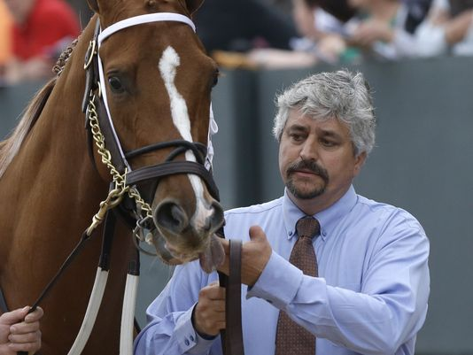 Thoroughbred trainer Steve Asmussen leads Tapiture to the paddock before the Rebel Stakes. Asmussen has been accused of cruelty to race horses by PETA. Photo: Danny Johnston/AP.