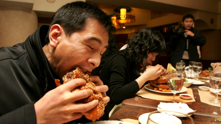 A Chinese man and a woman eat hamburger during a Burger King contest in XiAn. AP Image.