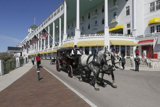 A carriage leaves the Grand Hotel in Mackinac Island, Mich. Horses do the heavy lifting on the island, hauling people and cargo across the car-free tourist destination in northern Michigan. Many of the 500 horses that are so vital to the island's operations during the warm-weather months spend winter on farms.