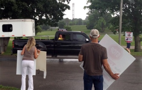 FOSH President Teresa Bippen is nearly run down and possibly killed by a black truck pulling a trailer during a peaceful protest of horse soring at a Big Lick event in Columbia, Tennessee. That's Teresa in the pink top on the right, behind the sign she is holding up. Photo: Billy Go Boy.