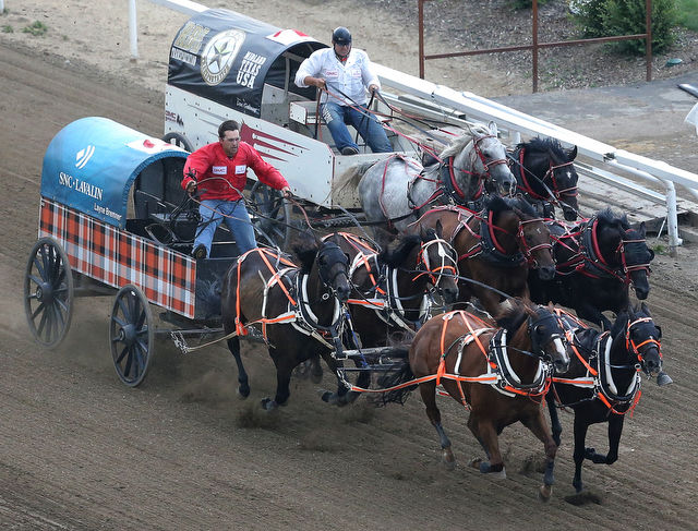 Layne Bremner (left) wins a race to the finish line with Dave Galloway (right) in the first heat of the Rangeland Derby in chuckwagon action at the Calgary Stampede on Saturday July 11, 2015. Stuart Dryden / Calgary Sun / Postmedia Network.