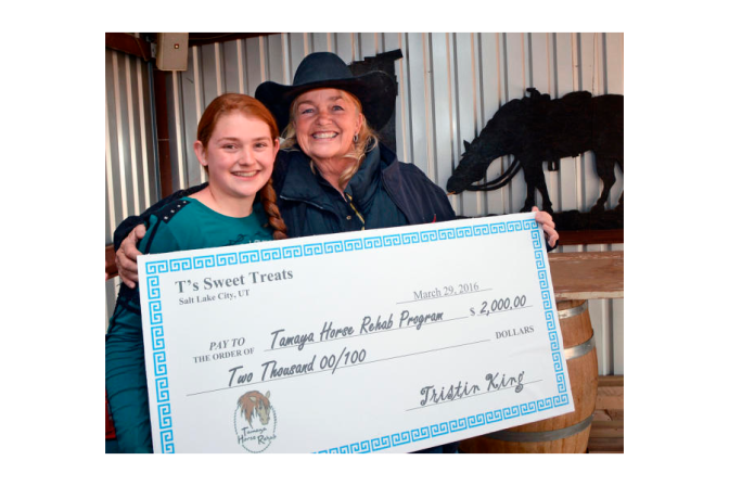 Tristin King gives $2,000 that she earned through her business, T's Sweet Treats, to Connie Collis, who runs the Tamaya Horse Rehab program. (Jim Thompson/Albuquerque Journal).