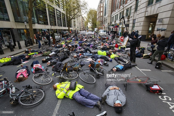 Photo Credit: Getty Images. Protesters stage a die-in protest with gas masks and teddy bears at an anti-pollution rally outside the Department for Transport in London, England to highlight the dangers of polluted air poses to people and childrens health.
