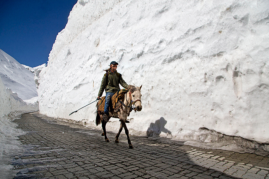 A Kashmiri man on a horse rides past walls of snow on the Zojila Pass, about 68 miles north of Srinagar, in Indian-controlled Kashmir, Saturday. The Srinagar-Leh national highway connecting Ladakh to the Kashmir Valley was re-opened to traffic Saturday after remaining closed for nearly six months. Dar Yasin/AP
