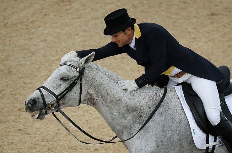 Shane Rose, of Australia, rubs Cp Qualified after competing in the equestrian dressage competition at the 2016 Summer Olympics in Rio de Janeiro, Brazil on Sunday.	John Locher/AP.