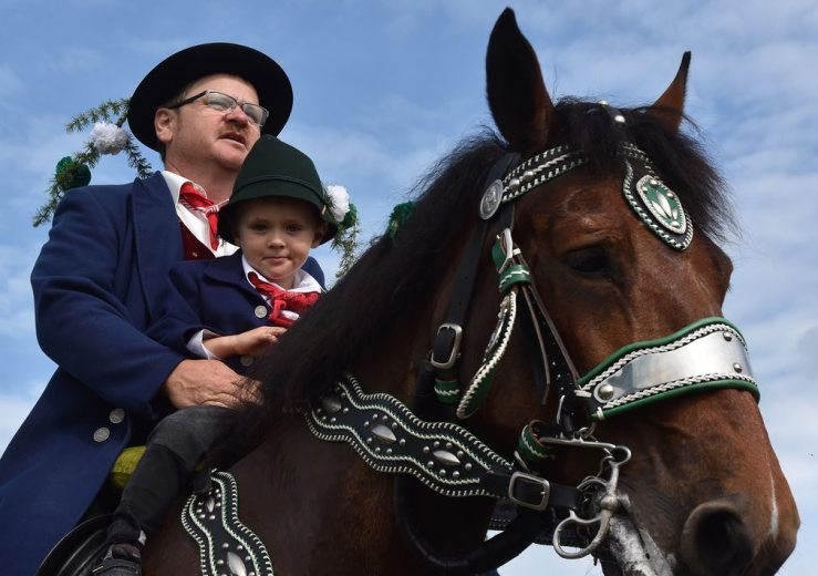 A man and a boy in traditional Bavarian costume ride through the village during Pfingstritt, a Pentecostal parade dating back to 1412. Photograph: Christof Stache / AFP / Getty Images.