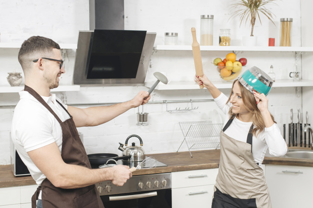 Couple having fun fight in kitchen. Freepix.