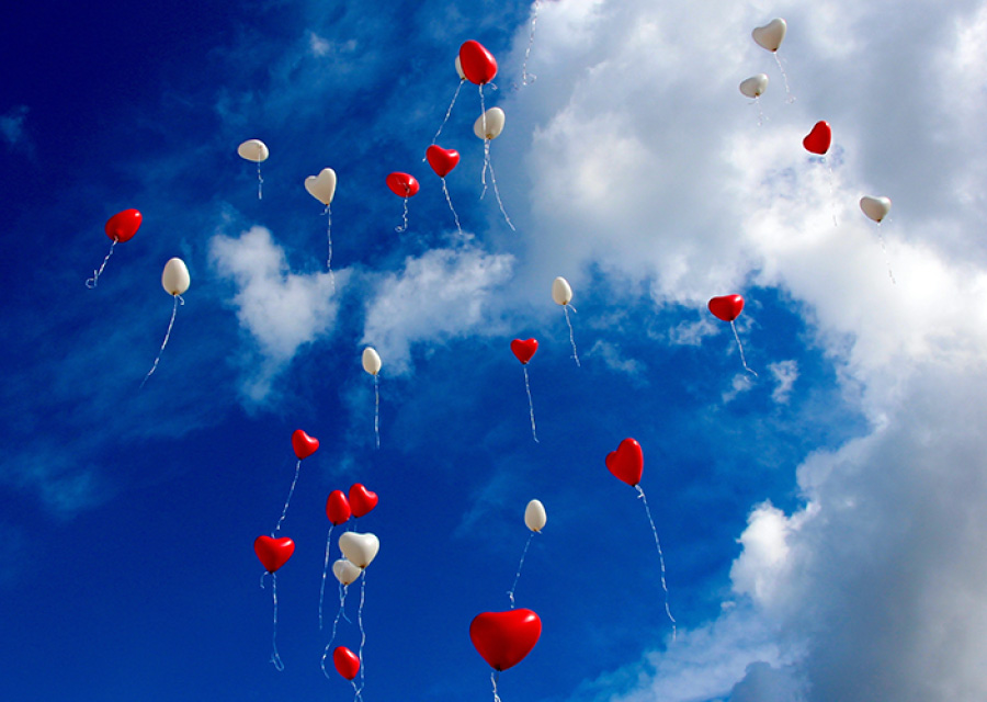 Blue sky and white fluffy clouds with red and white balloons.