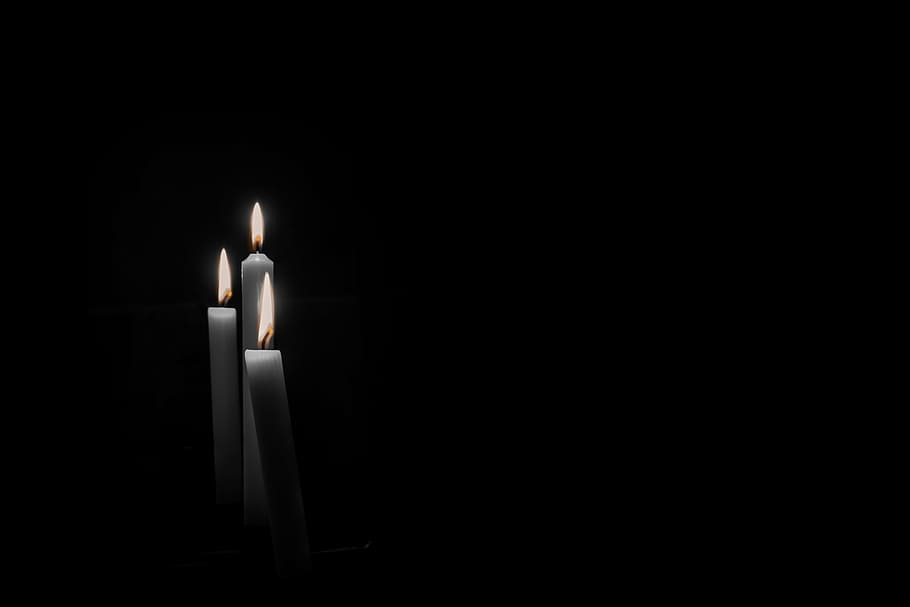 Three lit candles against black background.