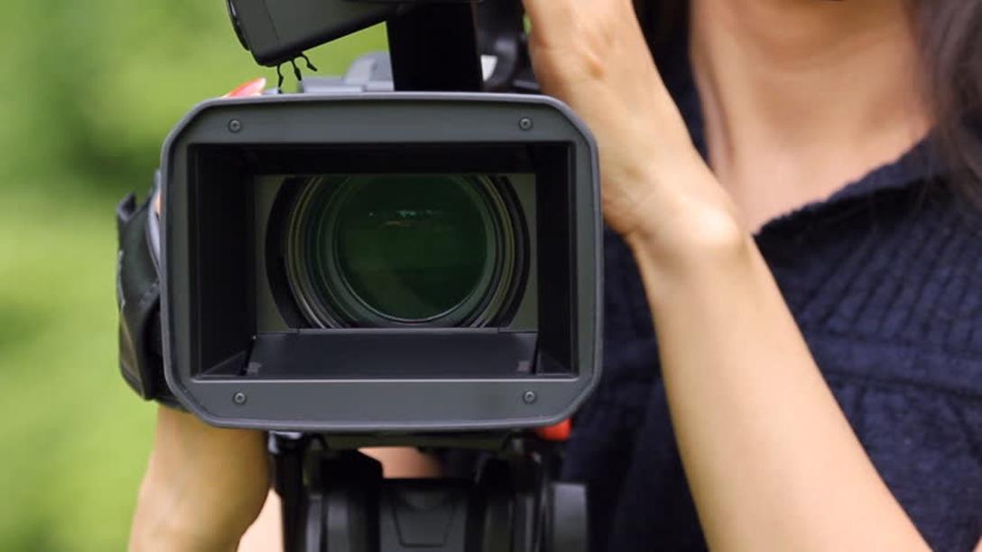 Woman using a video camera. Shutterstock.