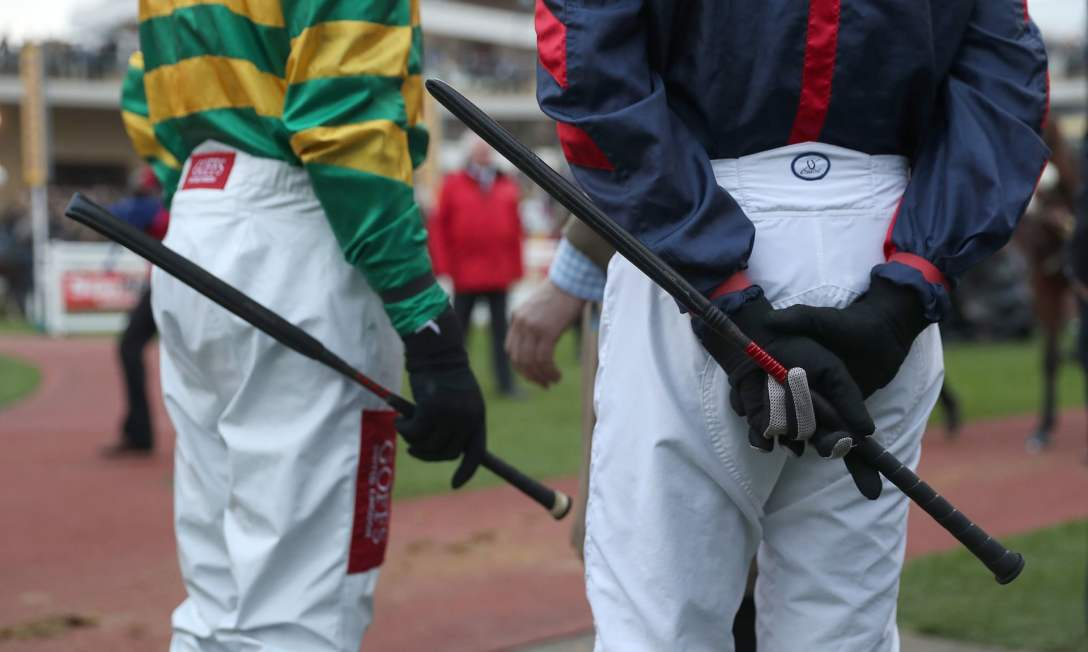 British jockeys stand in the paddock holding their whips. Image by David Davies/PA.