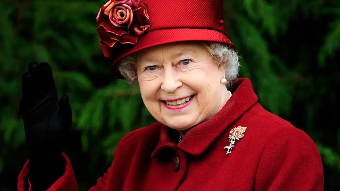 A waving Queen Elizabeth II in crimson red.