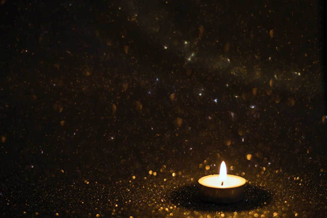 Burning votive candle against dark background.