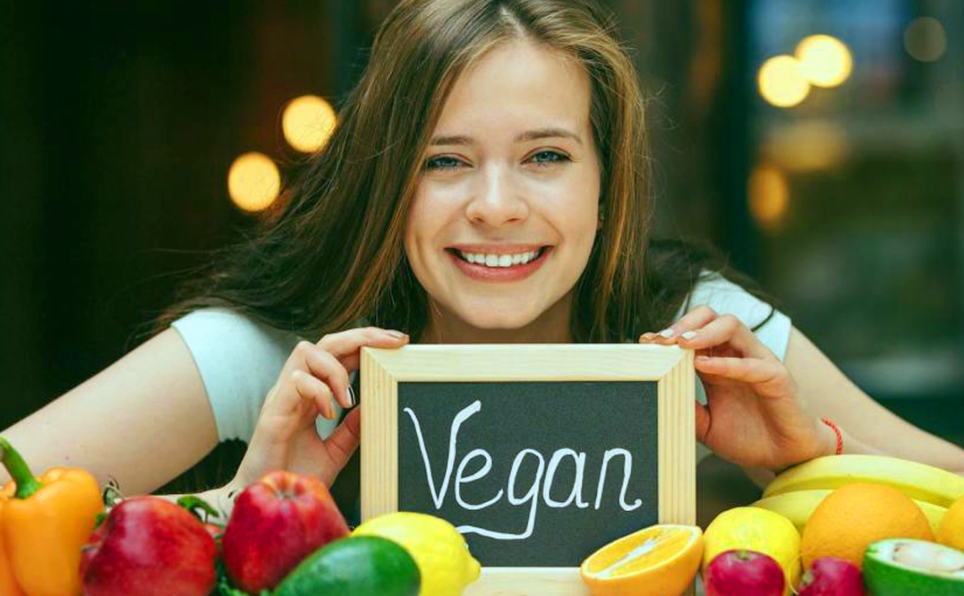 Smiling girl holding small chalkboard with Vegan written on it. Source: Unknown.